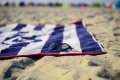 Голубое и белое большое пляжный полотенце и черные солнечные очки на песке Стоковое Изображение
