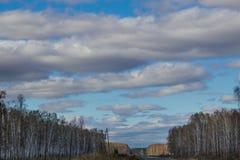 Голубое небо в облаках и дороге, идя прочь в расстояние стоковые фото