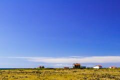 Голубое небо над полем и дома в Исландии Стоковое Изображение