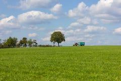 голубое небо с облаками и зеленым полем и трактор на горизонте стоковые фотографии rf