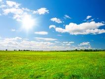 голубое пасмурное солнце неба зеленого холма под whit Стоковые Фото