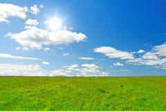 голубое пасмурное солнце неба зеленого холма под whit Стоковые Фотографии RF