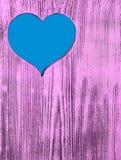 Голубое сердце высекаено в деревянной доске пурпура Справочная информация Стоковые Фото