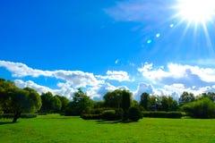 Голубое ясное небо ` S солнца излучает над парком, зеленой травой и деревьями Стоковая Фотография