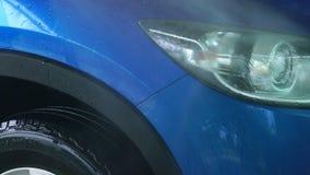 Голубой автомобиль компакта SUV с стиркой спорта и современного дизайна с брызгом воды от высокой шайбы давления на самообслужива