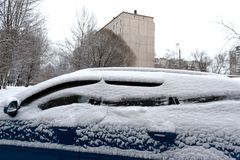 Голубой автомобиль тяжело покрытый со снегом Проблема удаления снега стоковые фото