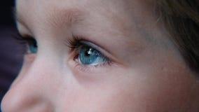 Голубой глаз красивого ребенка с длинным макросом ресниц снял видеоматериал