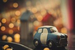 Голубой и белый милый автомобиль мультфильма на оранжевой предпосылке bokeh Концепция подержанного автомобиля Модель автомобиля и стоковое изображение