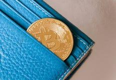 Голубой кожаный бумажник на темной предпосылке при одна золото и монетка bitcoin падая из их карманн Концепция секретного c стоковое изображение rf