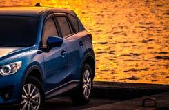 Голубой компактный автомобиль SUV со спортом и современным дизайном припаркованный на конкретной дороге морским путем на заходе с стоковые изображения rf