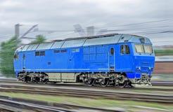 Голубой локомотивный тепловозный поезд на высокой скорости едет рельсом Стоковая Фотография