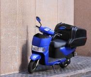 Голубой мотоцикл мопеда на выстилке города Стоковые Изображения RF