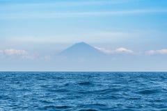 Голубой океан с ясными небом и горой Agung на предпосылке тюкованный Стоковое Изображение RF