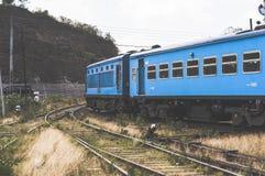 Голубой поезд вдоль гор стоковое фото rf