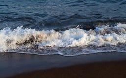 Голубой прилив морской воды на темном вулканическом пляже Расслабляющий прибой волны моря над seashore Стоковая Фотография