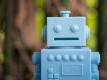 Голубой ретро робот забавляется на естественной зеленой предпосылке листьев Стоковое фото RF