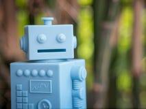 Голубой ретро робот забавляется на естественной зеленой предпосылке листьев Стоковое Изображение