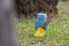 Голубой ретро робот забавляется с садовыми инструментами в естественных зеленых листьях Стоковые Изображения