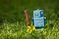 Голубой ретро робот забавляется с садовыми инструментами в естественных зеленых листьях Стоковые Фотографии RF