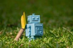 Голубой ретро робот забавляется с садовыми инструментами в естественных зеленых листьях Стоковое Изображение