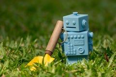 Голубой ретро робот забавляется с садовыми инструментами в естественных зеленых листьях Стоковое фото RF