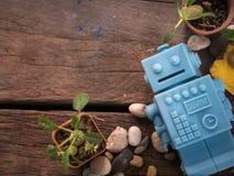 Голубой ретро робот забавляется с садовыми инструментами и деревянной картиной o пола Стоковые Изображения