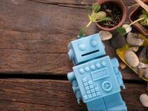 Голубой ретро робот забавляется с садовыми инструментами и деревянной картиной o пола Стоковая Фотография
