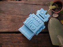 Голубой ретро робот забавляется с садовыми инструментами и деревянной картиной o пола Стоковое Изображение