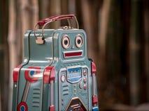 Голубой ретро робот забавляется с садовыми инструментами и деревянной картиной o пола Стоковое Изображение RF