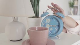 Голубой старомодный будильник звеня в утре Милая сонная женщина поворачивая будильник Утреннее время сток-видео