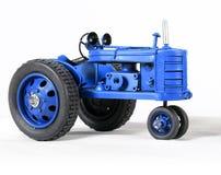 Голубой трактор игрушки на белизне стоковое изображение rf