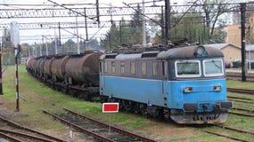 Голубой электрический локомотив при фуры масляного бака железнодорожные driing на железнодорожном вокзале Груз транспорта рафинад Стоковые Изображения