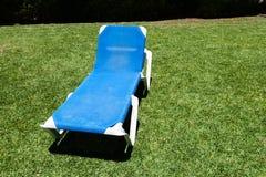 Голубой lounger на зеленой лужайке Стоковое фото RF