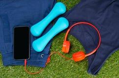 Голубой sportswear, гантели для фитнеса и мобильный телефон с красными наушниками, на фоне травы Стоковое Изображение RF