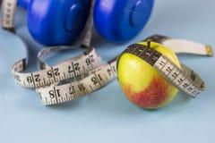 Голубые гантели, измеряя лента и яблоко на голубой предпосылке стоковые изображения rf