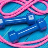 Голубые гантели и розовая гимнастическая прыгая веревочка на голубых досках, концепция Стоковое Фото