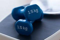 Голубые гантели na górze масштаба веса на деревянной предпосылке в спортзале Стоковые Изображения