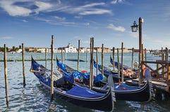 Голубые гондолы в Венеции и взгляде моря и дворца на заходе солнца Стоковые Изображения