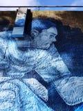 Голубые граффити человека в паркуя стене в Окленде стоковая фотография rf