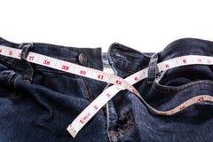 Голубые джинсы и белая измеряя лента на белой предпосылке Диета и стоковые изображения