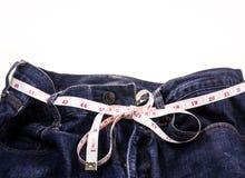 Голубые джинсы и белая измеряя лента на белой предпосылке Стоковые Фото
