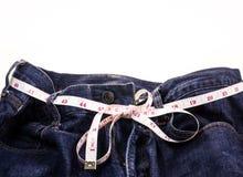Голубые джинсы и белая измеряя лента стоковые фото