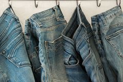 Голубые джинсы на вешалке, концепции моды дела стоковая фотография