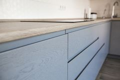 Голубые и белые шкафы в современном интерьере кухни стоковое изображение