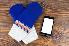 Голубые и белые knited mittens с мобильным телефоном на деревянной предпосылке стоковая фотография
