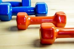 Голубые и красные гантели для здорового образа жизни, для тренировок утра и спорт дома Стоковое Изображение