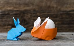 Голубые и оранжевые кролики Origami с яичком Стоковое Фото