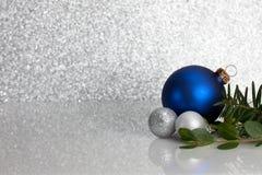 Голубые и серебряные орнаменты Кристмас на ярком блеске Стоковое фото RF