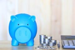 Голубые копилка и стог денег монеток на предпосылке wooder, деньгах сбережений для подготавливают в будущем и концепции вклада стоковые изображения