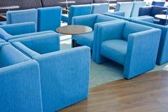 Голубые мягкие кресла и софы и круглые деревянные столы в горячем стоковые изображения